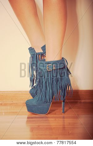 long slim woman legs in blue  ankle high heel fringe boot indoor shot on parquet against wall retro colors