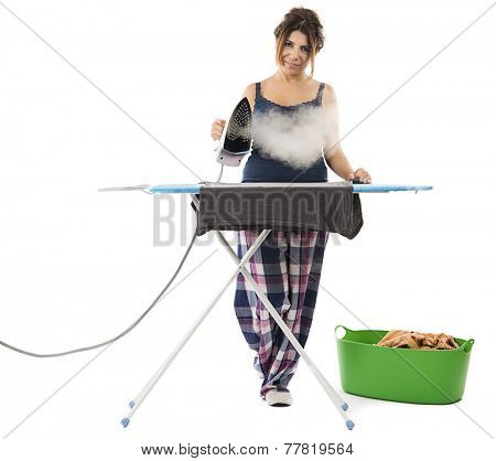 Cheerful housewife with a beautiful smile standing at the ironing board ironing clothes .