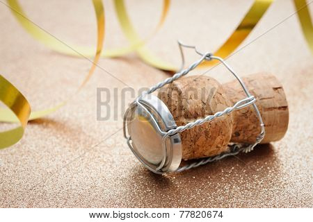 Cork from champagne bottle with streamers on golden background