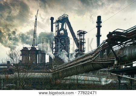 Smokestacks in factory with yellow smoke and clouds