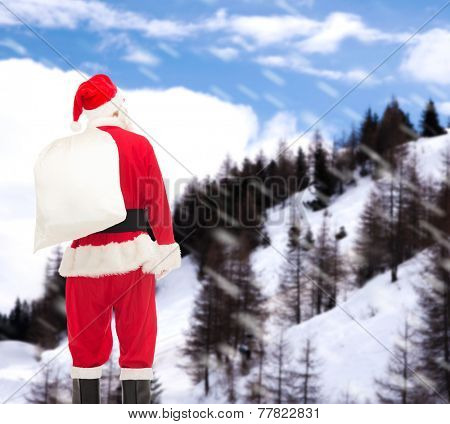 christmas, holidays and people concept - man in costume of santa claus with bag from back over snowy mountains background