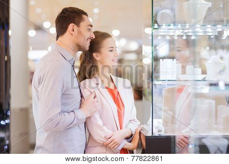 sale, consumerism and people concept - happy couple pointing finger to shopping window at jewelry store in mall