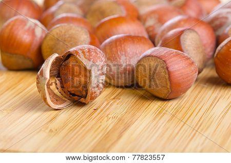 Hazelnut kernel inside shell on wooden background