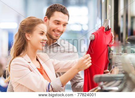 sale, consumerism and people concept - happy young couple with shopping bags choosing dress in mall