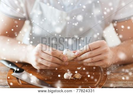 cooking, food, people and home concept - close up of male hands taking off peel of garlic on cutting board in kitchen