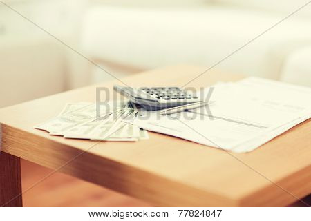 savings, finances, economy and home concept - close up of money with papers and calculator on table at home
