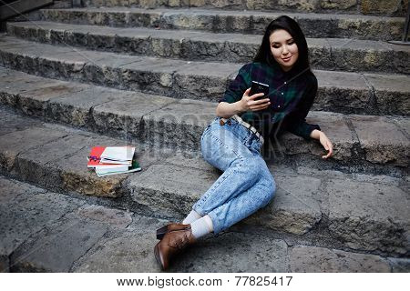 Young asian student using mobile phone during her class break