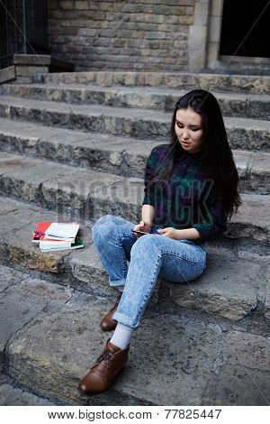 Attractive student girl using a smart phone sitting on the steps