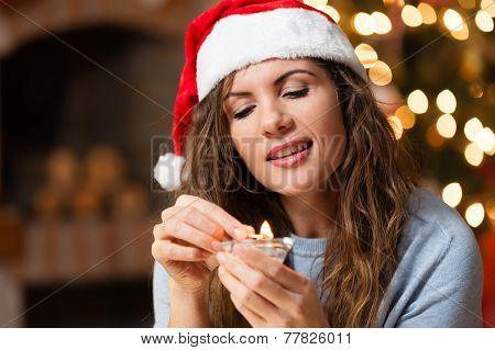 Young woman holding a small candel