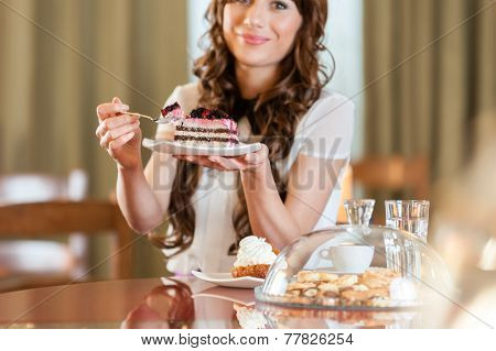 Pretty smiling woman enjoying fruit cake