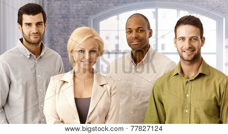 Closeup portrait of confident young businesspeople, smiling, looking at camera.