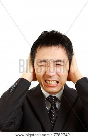 businessman holding hands on his ears