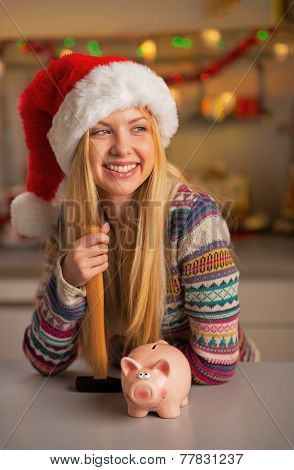Portrait Of Smiling Teenager Girl In Santa Hat With Piggy Bank A
