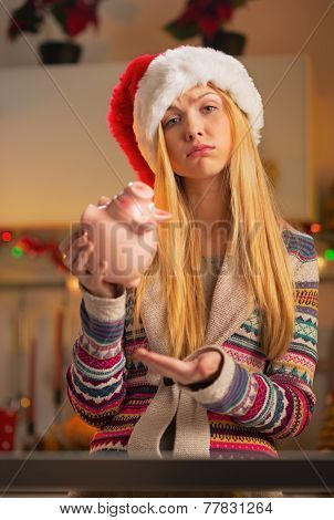 Portrait Of Displeased Teenager Girl In Santa Hat With Piggy Ban