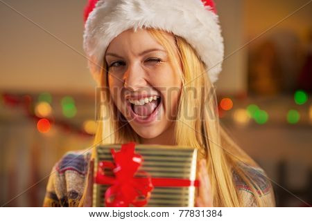 Winking Teenage Girl In Santa Hat Holding Christmas Gift