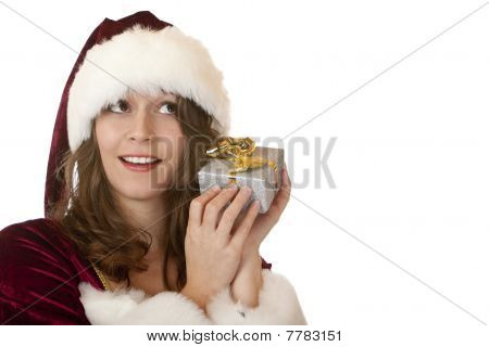 Young women in Santa Claus dress is holding a Christmas present on her ear to find out what is insid