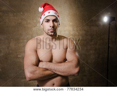 Serious Man With Santa Claus Hat Looking At Camera.