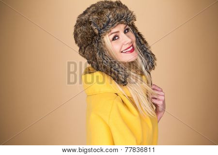 Pretty smiling blond woman with a lovely vivacious smile wearing a stylish winter fur hat and elegant yellow top on a brown studio background