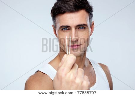 Sexy man holding tweezers over gray background