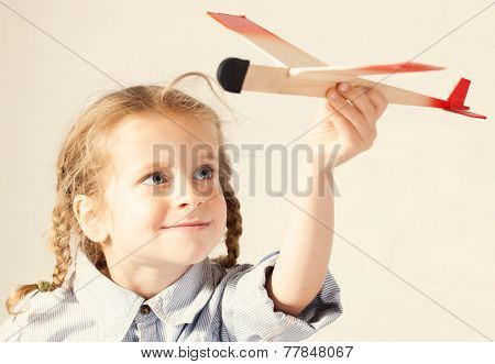Child playing with toy. Girl with plane