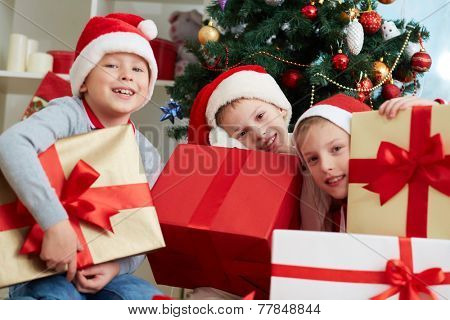 Three little boys in Santa caps holding big giftboxes