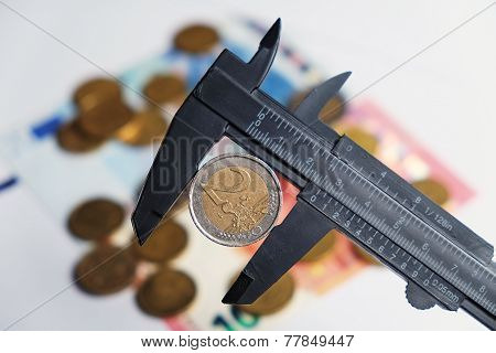 Two Euro coin being hold by a vernier tool