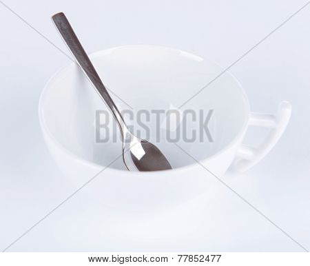 Empty cup with tea spoon isolated on white