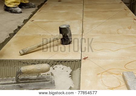 Close up of a workman's tools on a floor that is being tiled.