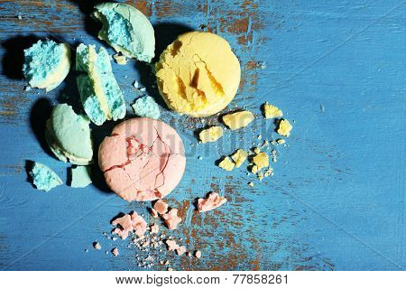 Bright tasty broken macaroons cakes on old wooden background