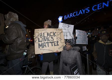 Activists with signs & Barclays Center background