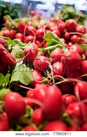 Stacks of fresh red radishes arranged in a supermarket