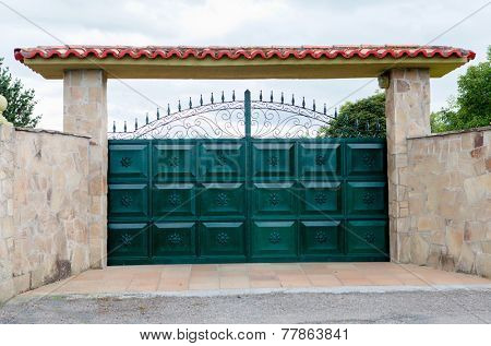 Iron gate with stone wall to enter a property