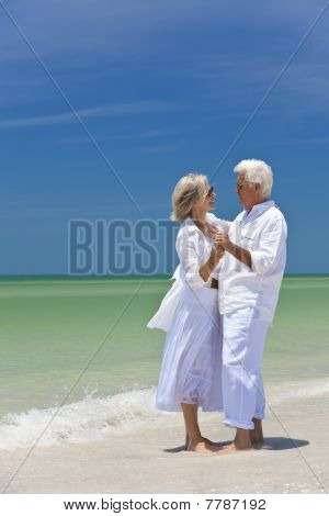 Happy Senior Couple Dancing, Hand in Hand an einem tropischen Strand