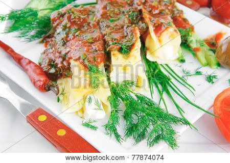 cannelloni in yellow cheese served on square white plate
