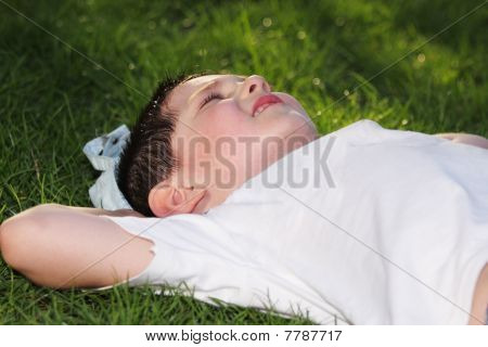 Boy Laying Down In Grass
