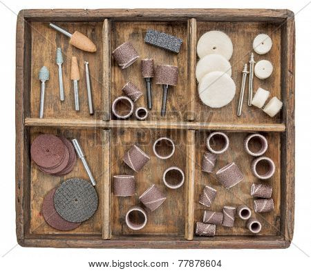 rotary tool accessories in wooden rustic box isolated on white