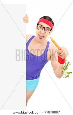 Nerdy man in sportswear eating carrot behind panel isolated on white background