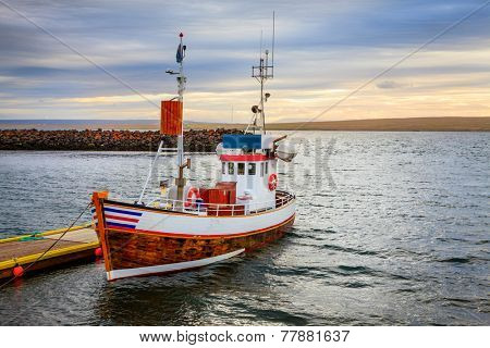 A small fishing boat at the pier in a small port in Northwestern Iceland