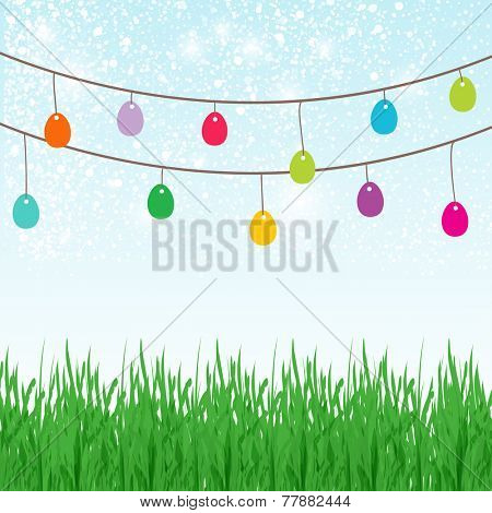 Easter background with place for text in the sky and  different colors painted Easter Eggs in the green grass.