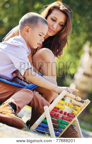 Mother teaches her son mathematics in the park