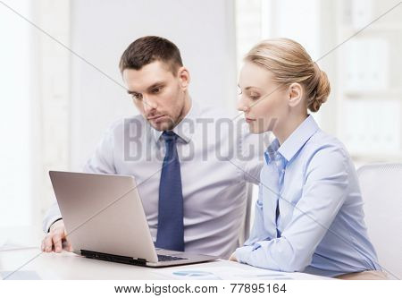 business and office concept - serious business team working with laptop computer in office