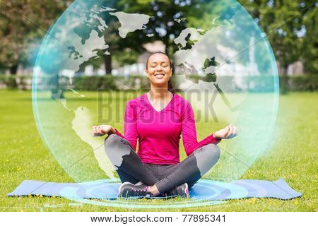sport, meditation, park and lifestyle concept - smiling woman meditating on mat outdoors