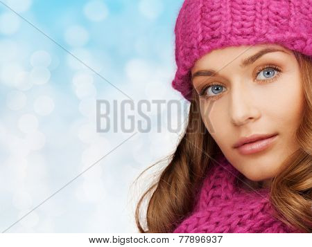 happiness, winter holidays, christmas and people concept - close up of smiling young woman in pink hat and scarf over blue lights background