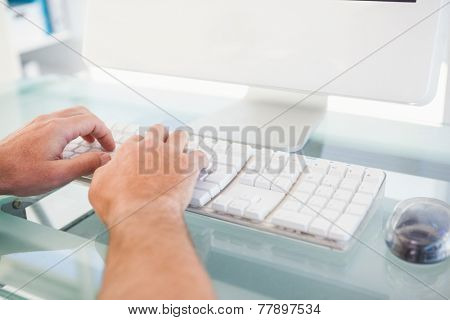 Close up of a man typing on keyboard in his office