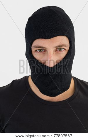 Portrait of burglar wearing a balaclava on white background