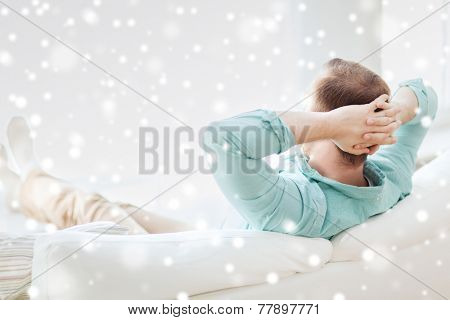 home, leisure, relax and happiness concept - man lying or sitting on sofa at home from back