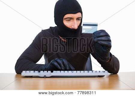 Burglar typing on keyboard and holding credit card on white background
