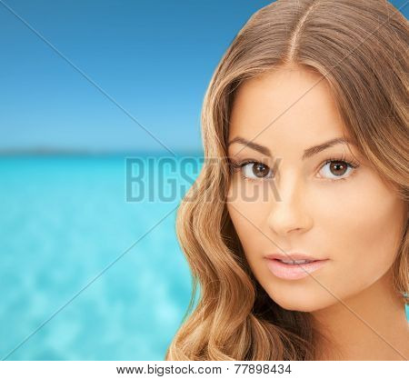 beauty, people, vacation and health concept - beautiful young woman face over blue sea and sky background