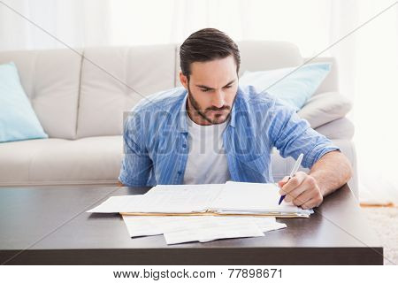 Focused man paying his bills in the living room