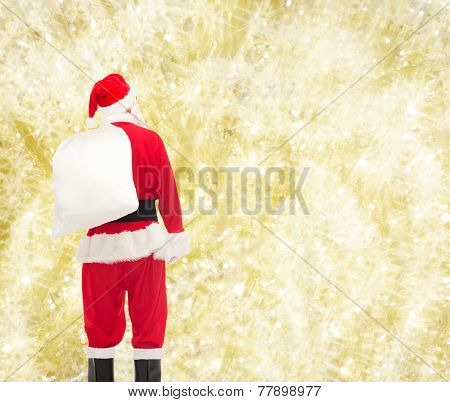 christmas, holidays and people concept - man in costume of santa claus with bag from back over yellow lights background